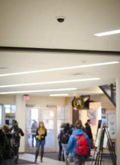 Jesse Hart | Argonaut Students on the second floor of the University of Idaho Commons walk below a surveillance camera. An institution-wide policy is being proposed to create standards regarding the surveillance equipment and various privacy protection guidelines.