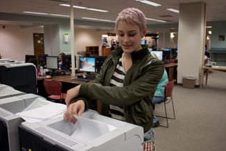 Amy Asanuma | Argonaut Junior Emily Forsberg sifts through paper in search of an essay at the campus library. ITS and the Sustainability Center worked to establish default front-back printing campus-wide.