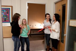 Michelle Wilson, Madison Farley, Chalayne Hoagland and Laura Monroe of the Lactation Resources Committee hold the red ribbon for the unveiling of a lactation room Apr. 11. The room, 201-A, is located on the second floor of the Education building.