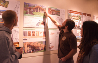 Jackson Flynn | Argonaut Senior architecture students Derek Oliver (left), Kyle Jones, and Adriana De Giuli (right) admire the architecture graduate students' work displayed in the Reflections Gallery. The winner of the competition is Kayla Stoker, second place went to Jacob Liddicoat and third place went to Tucker Haderlie.