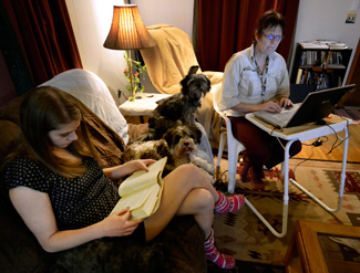 Amelia C. Warden Lisa Cochran (right) works on a presentation for her class while her daughter Madysen (left), 16, reads a book for school in the living room of their home in Moscow, Tuesday, Dec. 2, 2014.