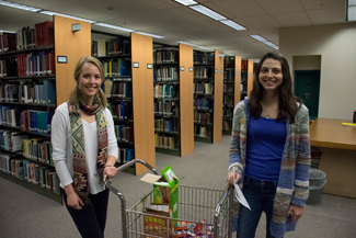 Brenda Ely| Argonaut Alysha Van Zante (left) and Zoe Ball (right) push around the free snack cart in the library Tuesday night.