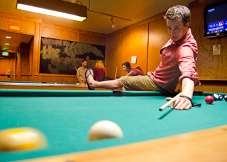 Nathan Romans | Argonaut  Byron Flood gets creative in a game of pool during Blue Monday at the Garden Lounge on Main Street.