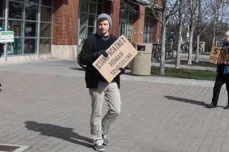 Genie Tran | Argonaut Nick Renn holds a sign outside the Commons Rotunda to help  raise awareness of human trafficking.