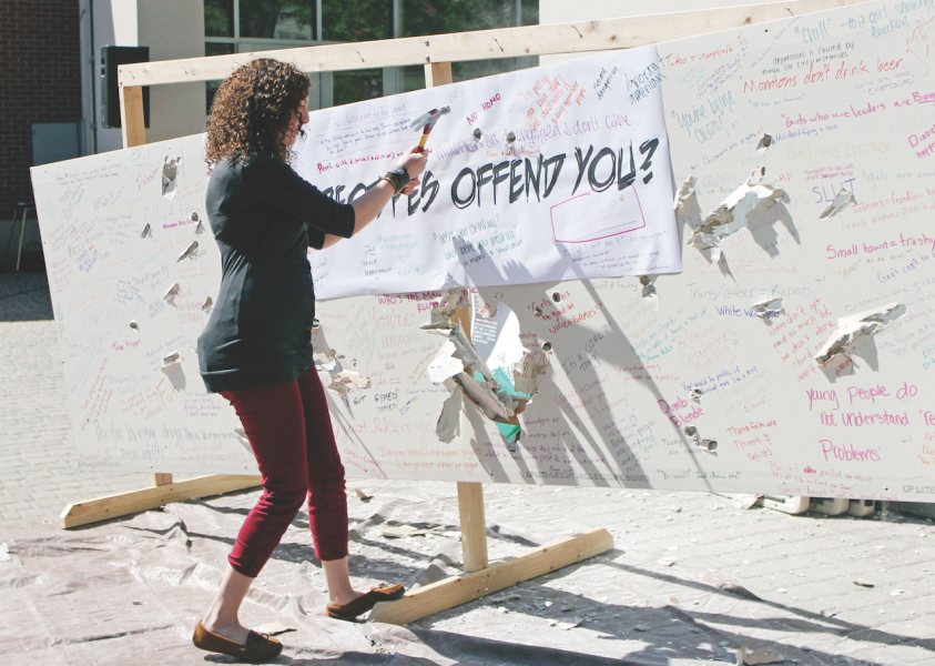 Diamond Koloski | Argonaut University of Idaho senior Heather Colwell helps destroy the wall at the Writing on the Wall event at the Idaho Commons Plaza Wednesday. The aim of the event was to symbolically tear down hateful stereotypes with the wall.