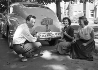 UI Library Special Collections | Courtesy Students pose with homecoming bumper sticker in 1949. In the years following World War II, the University of Idaho experienced growth as students strived to return to more normal circumstances. Traditional college activities, such as homecoming, enjoyed renewed popularity.
